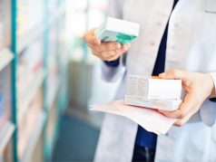 Pharmacist's hands taking medicines from shelf