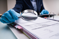 Business Fraud Investigation With Magnifying Glass In Gloves