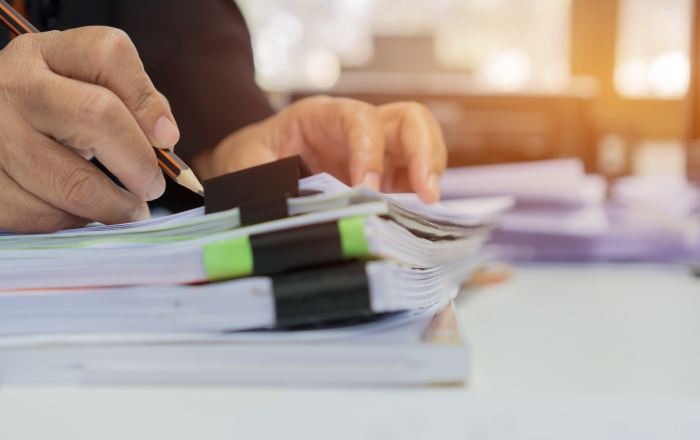 Accounting planning budget report file concept : Business woman offices check working for arranging documents unfinished stack of document papers with pen on busy office desk. Ideas for paperwork.