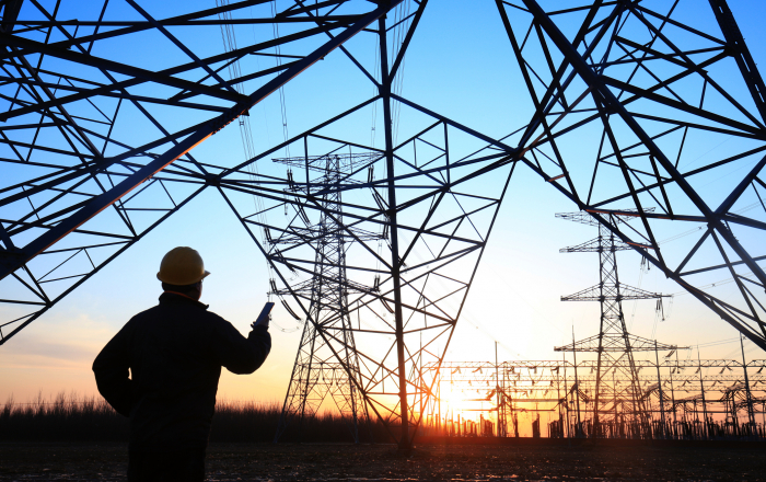 Electricity workers and pylon silhouette