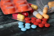 Pills and capsules on dark wooden table, a lot of multicolored medication close-up