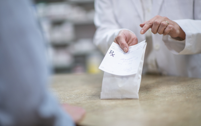 Pharmacist Holding Out a Packaged Prescription stock photo