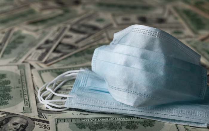 Medical face mask and dollar banknotes, world coronavirus finance, epidemic and economic losses concept.