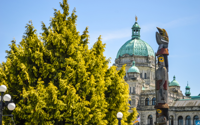 The Victoria government building beside an aboriginal totem pole.